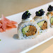 Nahaufnahme von Sushi für veganer, mit pflanzlichen Lebensmitteln wie Avocado, Frühlingszwiebeln, veganes Tonno, veganer Kaviar und würzige Soße