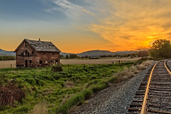 Homestead By The Tracks (http://fineartamerica.com/profiles/robert-bales.ht) Tags: emmett forupload haybales idaho people photo places projects states barn sunrise sunset house farm homestead ranch cattle barnwood fence butte squawbutte mountain landscape treasurevalley gemcounty scenicbiway americaphotography valley idahophotography beautiful sensational spectacular magnificent surreal sublime magical spiritual inspiring inspirational canonshooter scenic wow stupendous superb building grass hay trees yellow blue robertbales sky railroad tracks