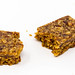 Broken cereal bar and crumbles by Hafervoll Flapjack with Mexican flavor, shot on white surface
