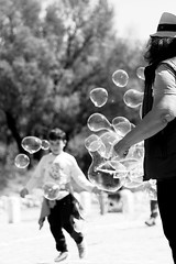 Don't grow up, it's a trap... (Michael Kalognomos) Tags: canoneos5dmarkiii canon ef24105mmf4l photography streetphotography streetstories streetlife boy child kid childhood bubbles balloons game blackandwhite bw monochrome people streetartist cinematography bokeh dof depthoffield greece athens acropolis