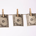 Hundred dollar bills bent in half hanging on clothes line