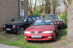 Laid up trio (doojohn701) Tags: red blue grey house laidup abandoned japanese green grass vegetation trees american british 4x4 nissan primera jeep cherokee landrover discovery shadow windows reflection sunlight sidcup uk