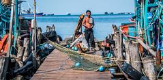 2019 - Cambodia - Sihanoukville - Tumnuk Rolok (Ted's photos - Returns late November) Tags: 2019 cambodia cropped nikon nikond750 nikonfx tedmcgrath tedsphotos vignetting dock pier two fishermen fishinggear net fishingnet shadow ropes boats boat tumnukrolok tumnukroloksihanoukville tumnukrolokcambodia sihanoukville sihanoukvillecambodia ក្រុងព្រះសីហនុ