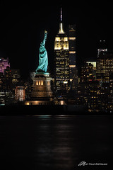 Standing in the Hudson (Matt Straite Photography) Tags: new york city downtown skyline skyscraper building tall statue liberty lady statueofliberty national america imagrant united states hudson toxic jersey shore water wet river rocks empire state empirestate tripod zoom canon night nocternal lights newyork