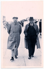 Two Men Walking in Skegness (pepandtim) Tags: postcard old early nostalgia nostalgic two men walking skegness 33tmw97 walfred photographers kiosk embassy grand parade hat cap raincoat