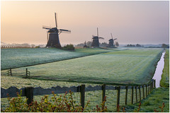 Three in a row at Leidschendam (Rob Schop) Tags: molendriegang leidschendam morning rijp frost cold sunrise windmill composition fence sonya6000 pola hoyaprofilters prime sigma30mm14 zuidholland color 52of2017