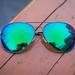 Blaugrüne Sonnenbrille auf einer Parkbank