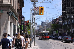 Toronto streetscapes: view east on Queen St. West - #2 (Jon Dev) Tags: streetphotography people pedestrians road cars streetcar tram buildings shops signs utilitypoles wires city urban downtown traffic infrastructure architecture ontario canada