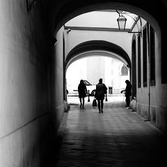 Passages (halifaxlight) Tags: slovakia bratislava downtown urban street pedestrians walking silhouettes arches van lamp windows bw square absoluteblackandwhite