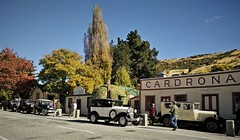all in a row (SM Tham) Tags: newzealand southisland crownrangeroad cardrona town cardronahotel building vintagecars road street autumn fall trees foliage sky mountainside streetscene people