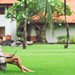 Woman online shopping concept. Woman in the green park with modern laptop. Bali island.
