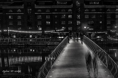 bridge to The Quay (Sy at sswhite11) Tags: canarywharf london buildings lights water bridge blackandwhite people