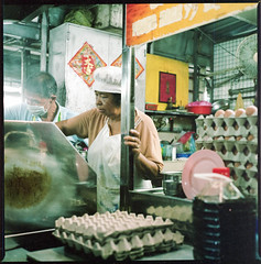 her booth (chtaudt) Tags: 2018 night dezember penang color ishootfilm street guerneydrivehawkercenter asia travel filmisnotdead iso800 malaysia reise 6x6 food hawkercentre nikkorpc75mmf28 mittelformat filmphotography zenzabronicas2a push georgetown mediumformat kodakportra400 pasembur strase foodmarket