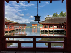 Itsukushima Shrine - Miyajima Island (Japan) (Andrea Moscato) Tags: andreamoscato giappone japan asia japanese 日本 nihon nippon asian light luce shadow ombre prefecture attraction ombra site national nature natura natural naturale landscape paesaggio day white sky cielo view vivid vista scenic blue parco park history historic ancient treasure wood art architecture monument brilliant water sea seascape seashore bay hiroshima unesco world heritage island isola seto inland setonaikai riflesso reflection tide lanterna buildings shore clouds morning red torii orange columns shrine shinto frame