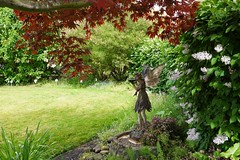 Woodland Fairy in the Lilac Garden (Linda on the bridge to NewWhere) Tags: art flower grass lilac naturalframe statue tree flickrlounge weeklytheme fairy