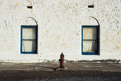 fireplug. death valley junction, ca. 2018. (eyetwist) Tags: eyetwistkevinballuff eyetwist red fireplug fire hydrant water peeling paint windows symmetry hotel amargosahotel deathvalleyjunction mojavedesert california nikon n90s nikkor 28105mmf3545d 28105mm kodak ektachrome e100 100 35mm new transparency chrome slide nikonn90s kodakektachromee100 ishootfilm ishootkodak analog analogue film emulsion coolscan iconla southwest usa deathvalley junction mojave desert amargosa opera martabecket historic landmark borax adobe window wall building weathered worn decay minimalist