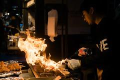 Flame burning street food in Myeongdong (kitsunekuma) Tags: seoul korea korean streetphotography streetfood street fujifilm fujinon fuji 35mm xpro1 xf xf35mmf2 flame sausage food burning lights light nightshot night myeongdong