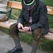 Mann in Tracht sitzt auf Parkbank und schaut aufs Handy