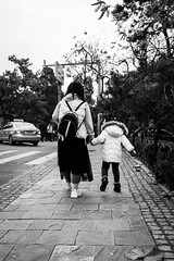 Levitation (Go-tea 郭天) Tags: qingdao shandong républiquepopulairedechine girl woman mother daughter family love together 2 little kid small lady back backside bag cold winter jump jumping illusion sidewalk pavement trees walk walking movement backpack coat dress young youth relationship car taxi street urban city outside outdoor people candid bw bnw black white blackwhite blackandwhite monochrome naturallight natural light asia asian china chinese canon eos 100d 24mm prime child