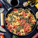 Cooking on a black background. Pasta with spices, vegetables and herbs. Top view