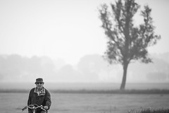 Early morning cyclist (Sjaco Manuputty) Tags: bicycle cyclist people man male cycling landscape street tree meadow candid bnw blackandwhite blackandwhitephotography netherlands