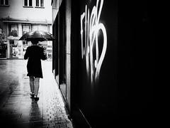 walking in the rain (Sandy...J) Tags: rain monochrom mood walking women grafitti urban umbrella noir city blackwhite bw street streetphotography sw schwarzweis strasenfotografie stadt olympus fotografie photography germany atmosphere absoluteblackandwhite