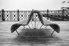 Seaside - Bendy Bench (julieloolibelle15) Tags: hastings 2019 may seaside shootfromthehip streets streetphotography england tradition documentary beach lifestyle summer towns people bench wood shapes lines monochrome blackandwhite abstract