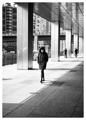 Lost in Thought (Dave Button) Tags: london canarywharf bw acros xe2 xe2s fuji fujifilm 27mm black white mono monochrome walking shadow light contrast street urban city girl woman