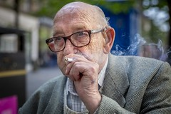 Lifetime (Leanne Boulton) Tags: urban street portrait portraiture streetphotography streetportrait streetlife closeup sociallandscape socialdocumentary characterportrait old elderly man male face eyes expression mood emotion smoke smoker smoking cigarette story tone texture detail depthoffield bokeh naturallight outdoor light shade city scene human life living humanity society culture lifestyle people canon canon5dmkiii 70mm ef2470mmf28liiusm color colour glasgow scotland uk