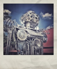 Detail of Folk Sculpture | Robot Lirpa-Anad-Nitsud* | Fischer Crossroads | Fort Payne, Alabama (steveartist) Tags: fakepolaroids fakeinstantphotos instantapp iphonese snapseed robot monumentalart folkart photostevefrenkel fischercrossroads fortpayneal folkartsculpture metalsculpture recycledmetalparts sky clouds leaves building