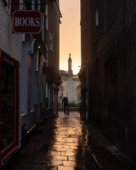 Cambridge Sunset (Scott Baldock) Tags: cambridge rain sunset cyclist bicycle wet alley book store dark reflection