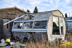 Winds blowing destroying the greenhouse now abanadoned (darletts56) Tags: sky blue cloud clouds white grass building buildings shed garage abandoned destroy destroyed window windows broken yellow buckets plant pots wood prairie village saskatchewan canada daylight
