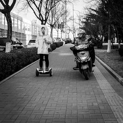 Speed racer (Go-tea 郭天) Tags: qingdao shandong républiquepopulairedechine man woman lady young cold winter sun sunny helmet motorbike motorcycle uniform delivery delivering speed fast movement transportation duty business work working right race competition competing compete balance coffee hat left sidewalk 2 together electric smart pavement lines trees cup street urban city outside outdoor people candid bw bnw black white blackwhite blackandwhite monochrome naturallight natural light asia asian china chinese canon eos 100d 24mm prime