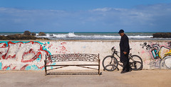 The Choice (Ash and Debris) Tags: africa guy bicycle graffity morocco bench water city bike citylife streetlife walk man urban ocean waves street urbanlife sky quay wall essaouira seaside