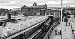 Nottingham (Peter Leigh50) Tags: blackandwhite mono monochrome grey station platform canopy roof railway railroad rail road lamp post chimney clock people signal train dmu class 156 fujifilm fuji xt2 town townscape city