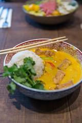 Gelbes Kokos-Tofu-Curry als asiatisches veganes Mittagessen mit Duftreis, Blumenkohl & Babyspinat, in einer Schüssel mit Essstäbchen, auf einem Holztisch (verchmarco) Tags: food lebensmittel noperson keineperson vegetable gemüse lunch mittagessen dinner abendessen bowl schüssel meal mahlzeit dish gericht meat fleisch cooking kochen delicious köstlich rice reis traditional traditionell plate teller cuisine grow wachsen nutrition ernährung chicken hähnchen pork schweinefleisch fish fisch2019 2020 2021 2022 2023 2024 2025 2026 2027 2028 2029 2030 harbour truck interior windows historic ciel outside owl españa shop