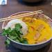 Gelbes Kokos-Tofu-Curry als asiatisches veganes Mittagessen mit Duftreis, Blumenkohl & Babyspinat, in einer Schüssel mit Essstäbchen, auf einem Holztisch