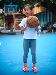 4-6 Yr Old Basketball English Lesson 21 (ArdieBeaPhotography) Tags: boy girl child kids children kindergarten preschooler elementary school age play basketball shoot throw catch pass toss ball leap jump tights white rainbow gauzy skirts trousers shorts shirt tshirt blue glasses court trees shadow leaves tummy navel button bare exposed sandals trainers shoes trackpants outside class learning teaching englishlesson black hair cute pretty beautiful handsome enthusiastic game energetic excited together tamronspaf2875mmf28xrdildasphericalif