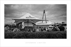 Afternoon libation (Parallax Corporation) Tags: southportpier seasidetown bulmers blackwhite canopy monochrome streetlife streetphotography cocacola cafe´ sonya7rii sonygmaster24mmf14 dayout holidaymakers tourists hedgerow beergarden millenniumbridge