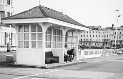 Seaside - A Seat in a Shelter (julieloolibelle15) Tags: hastings 2019 may seaside shootfromthehip streets streetphotography england tradition documentary beach lifestyle summer towns people shelter monochrome blackandwhite promenade