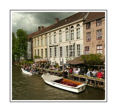 Boats at the hotel (Audrey A Jackson) Tags: panasonicdmctz3 bruges belgium canal boats hotel sky clouds trees people windows chimneys