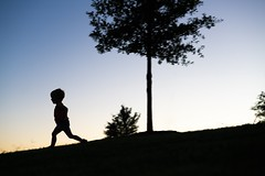 Milo Chasing His Silhouette (donnierayjones) Tags: grass tree dusk evening silhouette hill running run kid child boy
