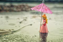 Singing in the Rain (flashfix) Tags: april192019 2019inphotos flashfix flashfixphotography ottawa ontario canada nikond7100 40mm character mario mariocharacter princesspeach rain water puddle figurine