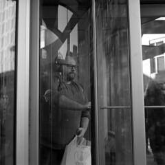 untitled (kaumpphoto) Tags: rolleiflex 120 tlr ilford bw black white city urban street man bag shop revolve glass exit glasses reflection push headphones door minneapolis