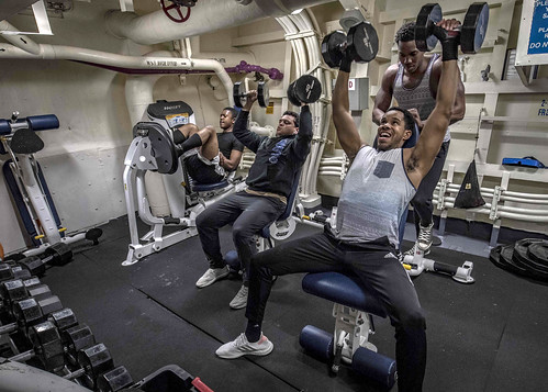Chief Information Systems Technician Ty Davis leads Sailors in a weight lifting class.