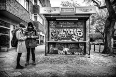 The Androids vs The Tabloids (Mister G.C.) Tags: blackandwhite bw sonya6000 sonyalpha6000 mirrorless streetphotography urbanphotography candid street monochrome people photograph image newspaperstand kiosk newspaper stand mobilephones cellphone smartphone handy graffiti unposed urban town city sony a6000 12mm ultrawide wide wideangle samyang rokinon f2 f20 primelens manualfocus schwarzweiss strassenfotografie berlin deutschland europe