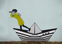 Looking For Paper Planes (Steve Taylor (Photography)) Tags: paperboat binoculars overcoat hood portholes mural graffiti green blue black white girl asia singapore pattern contrast boat ship