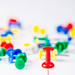 Set of push pins in different colors on white background