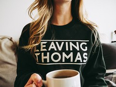 woman wearing black Leaving Thomas-printed sweater while holding white ceramic mug filled with coffee - Credit to https://myfriendscoffee.com/ (John Beans) Tags: coffee cafe coffeebeans shopbeans espresso coffeecup cup drink cappucino latte