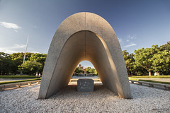 Hiroshima Victims Memorial Cenotaph (Japan) (Andrea Moscato) Tags: andreamoscato giappone japan asia japanese 日本 nihon nippon asian light luce green shadow ombre prefecture attraction ombra site national nature natura natural naturale landscape paesaggio day sun sunshine white sky cielo view vivid vista scenic blue parco park trees history historic ancient art giardino architecture monument tree brilliant unesco world heritage sites peace memorial sign structure afternoon memory sculpture city città gravel stone granite tunnel galleria sunset dusk